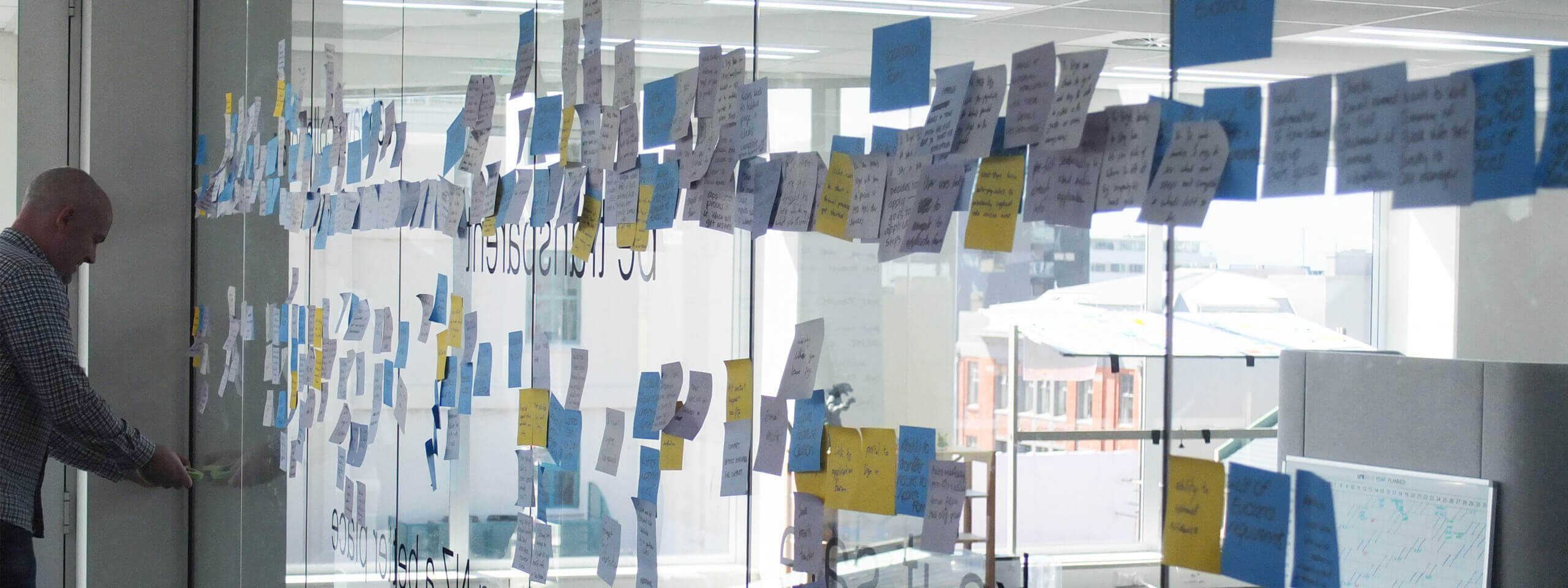 A project discovery workshop facilitator places post-its on a glass wall during user story mapping.