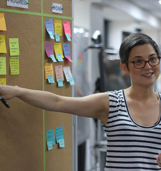 An Agile coach at a project board planning an Agile kick-off workshop with her team.